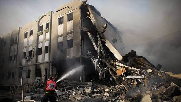 Firefighters in Gaza try to extinguish a fire at the Ministry of Interior after it was hit by an Israeli missile on Friday.
