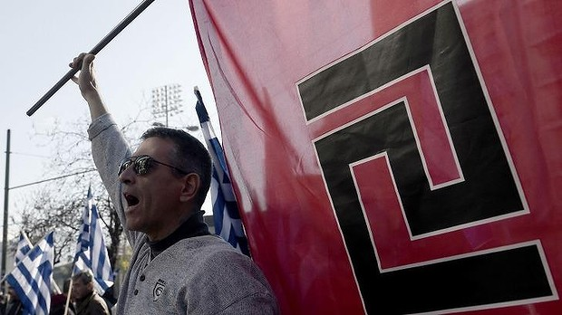 Supporters of ultra-nationalist party Golden Dawn shout slogans outside a courthouse in Athens.