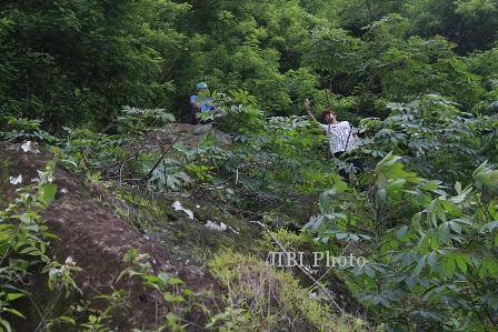 warga memantau batu seukuran rumah yang longsor dari tebing kapur setinggi 100-an meter, Kamis (16/1). Kondisi itu mengancam keselamatan 15 warga Mundon, Burikan, Cawas yang tinggal di bawah bukit itu. (JIBI/Solopos/Ashoquib Angriawan)
