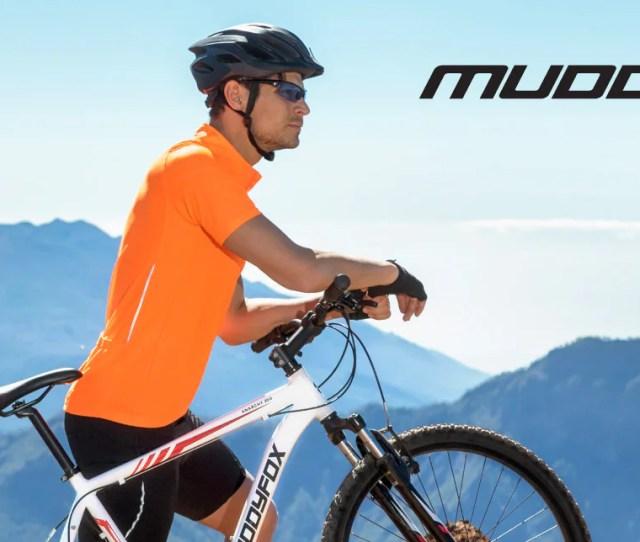 Man Wearing Orange Muddyfox Cycling Top With Black Helmet Sunglasses And White Muddyfox Bike On