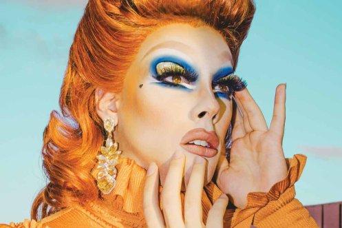 Etcetera Etcetera wearing orange hair and shirt with blue eye makeup