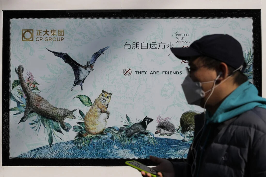 A man walks by a poster promoting the protection of wild animals in Beijing on March 11, 2020. Authorities have cracked down on the sale of wild animals for food. SCMP