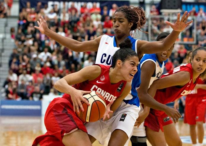 Canada's Kia Nurse, bottom, drives past Cuba's Francy Ochoa Izquierdo, top, during first half action at the 2015 FIBA Americas Women's Championship Final in Edmonton, Alberta, on Sunday, Aug. 16, 2015. (Jason Franson/The Canadian Press via AP)