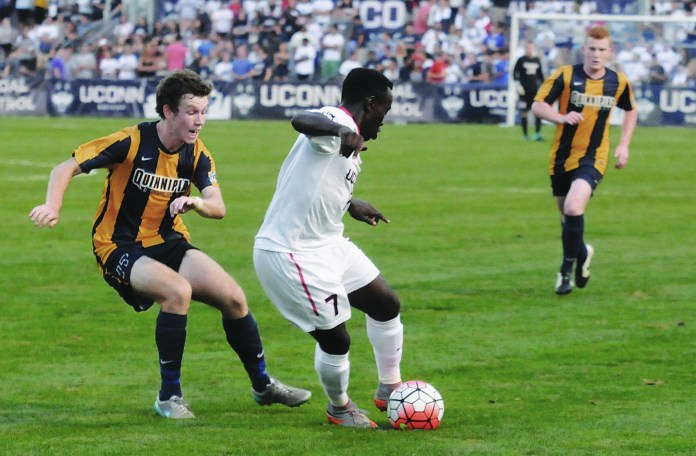 Junior Kwame Awuah (right) dribbles away from a Quinnipiac player at Joseph J. Morrone Stadium on Aug. 31, 2015. Awuah provided most of the Huskies' offensive life, firing three shots and nearly scoring.(Amar Batra/The Daily Campus)