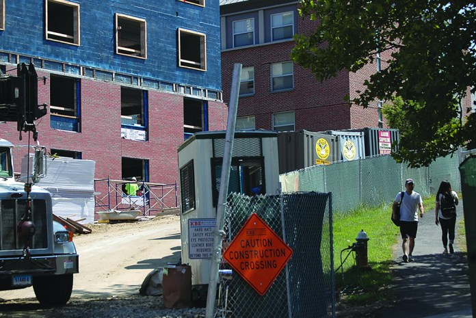 UConn students walk past construction on the new STEM residence hall near the Putnam Refectory on Sept. 1, 2015. Construction on the refectory is slated to begin in the coming weeks, with the dining hall scheduled to reopen in 2016. (Erika Elechicon/The Daily Campus)