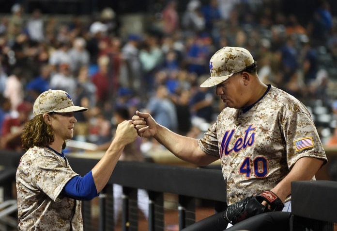 New York Mets starting pitcher Jacob deGrom congratulates starting pitcher Bartolo Colon (40) at the dugout after Colon struck out the Philadelphia Phillies side in the seventh inning of a baseball game at Citi Field on Monday, Aug. 31, 2015, in New York. (Kathy Kmonicek/AP)