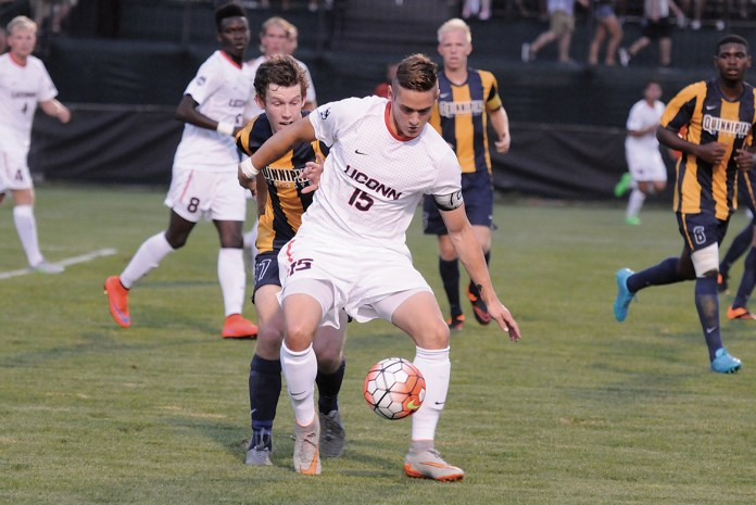 UConn men's soccer Jakob Nerwinski holds off a Quinnipiac player during the Huskies' game against the Bobcats on Monday, Aug. 31, 2015. (Amar Batra/The Daily Campus)