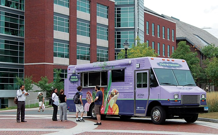 Students and staff members stand in front of the Food for Thought food truck on Fairfield Way. The truck has been well received since debuting a few weeks ago, UConn Dining Services said. (Ashley Maher/The Daily Campus)