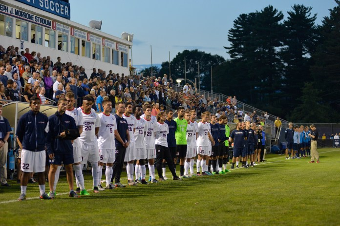 UConn men's soccer team players, coaches and staff stand on the sideline for a moment of silence honoring former head coach Joseph J. Morrone prior to the team's game against Rhode Island at the stadium that bears his name in Storrs, Connecticut on Saturday, Sept. 19, 2015. Morrone died Wednesday at the age of 79. (Jason Jiang/The Daily Campus)
