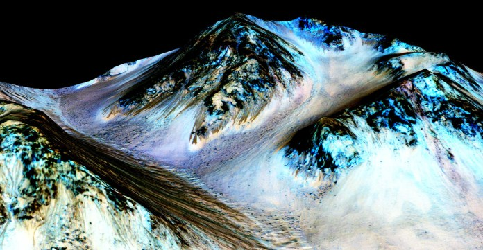 This undated photo provided by NASA and taken by an instrument aboard the agency's Mars Reconnaissance Orbiter shows dark, narrow, 100 meter-long streaks on the surface of Mars that scientists believe were caused by flowing streams of salty water. (NASA/JPL/University of Arizona via AP)