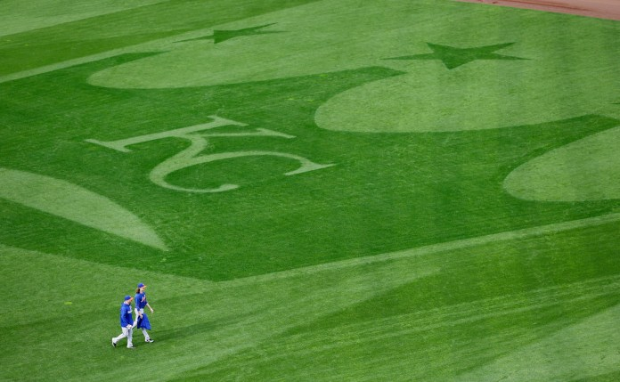 New York Mets starting pitcher Jacob deGrom, right, and bullpen catcher Dave Racaniello walk in the outfield during media day for the Major League Baseball World Series against the Kansas City Royals Monday, Oct. 26, 2015, in Kansas City, Mo. (David J. Phillip/AP)