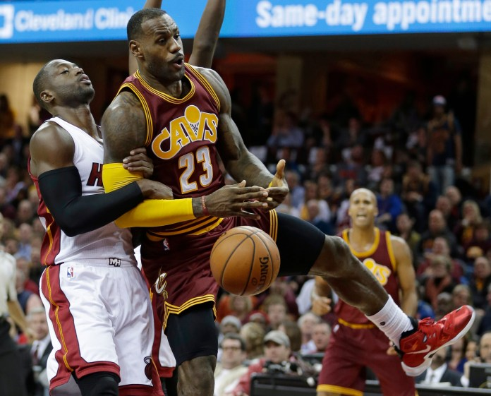 Miami Heat's Dwyane Wade, left, fouls Cleveland Cavaliers' LeBron James during the second half of an NBA basketball game Friday, Oct. 30, 2015, in Cleveland. The Cavaliers won 102-92. Wade and James were the key components of the 2nd longest winning streak in NBA history. (AP)
