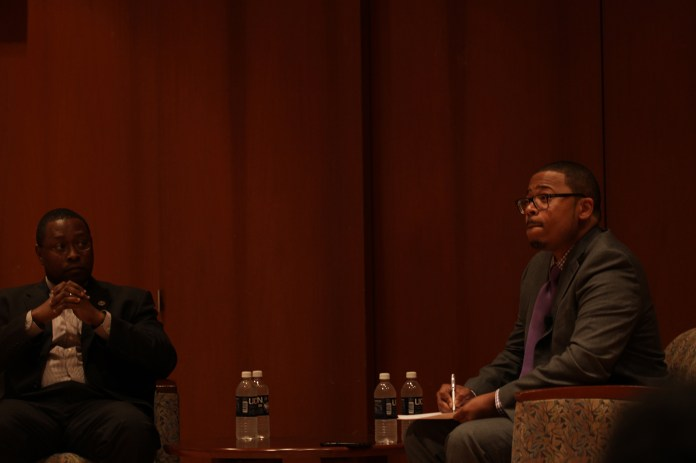 """UConn assistant professor Dr. Erik Hines (right) and Ohio State University distinguished professor Dr. James L. Moore III sit in the Konover Auditorium during the forum """"Black Males in Higher Education: A Conversation with Dr. James L. Moore III"""" on Thursday, Nov. 5, 2015. (Mei Buzzell/The Daily Campus)"""
