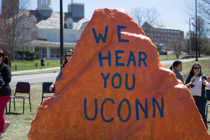 """During an event at the Spirit Rock in April 2015, students gathered in response to a """"Black Lives Matter"""" message on the rock being defaced. The word """"Black"""" was painted over. The above message signaled inclusion on the UConn campus. (Rebecca Newman/The Daily Campus)."""