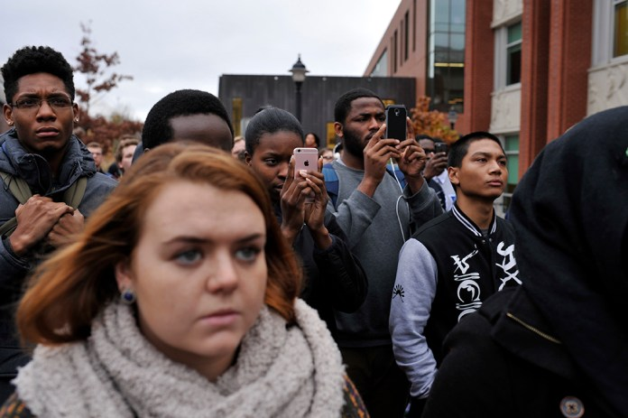 Students are seen watching the demonstration and recording on their phones on Fairfield Way in Storrs, Connecticut on Thursday, Nov. 19, 2015. (Jason Jiang/The Daily Campus)