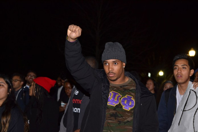 """UConn student Josh Marriner, also a running back on the UConn football team, holds up a fist while walking in the """"March for Justice, Empowerment and Solidarity""""on Fairfield Way in Storrs, Connecticut on Thursday, Nov. 19, 2015. (Amar Batra/The Daily Campus)"""