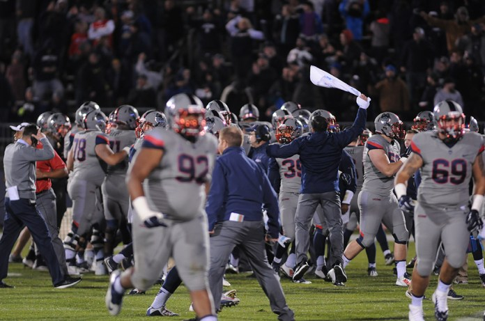 Members of the UConn football team celebrate after upsetting No. 13 Houston at Pratt & Whitney Stadium at Rentschler Field in East Hartford, Connecticut on Saturday, Nov. 21, 2015. The win made the Huskies bowl eligible for the first time since 2010. (Amar Batra/The Daily Campus)