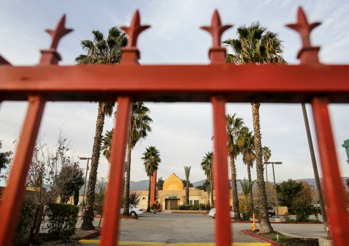 The Dar Al Uloom Al Islamiyah of America is viewed through a gate, Thursday, Dec. 3, 2015, in San Bernardino, Calif. A heavily armed man and woman opened fire Wednesday on a holiday banquet for his co-workers, killing multiple people and seriously wounding others in a precision assault, authorities said. Hours later, they died in a shootout with police. (Ringo H.W. Chiu/AP)