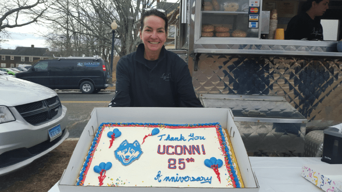 """Lizzie Searing of Lizzie's Catering and Lizzie's Curbside, the well-known food truck often parked outside of the Arjona Building, holding her """"thank you"""" cake marking her 25 years on campus. Cake and coffee was free this morning as part of the celebration.(Annabelle Orlando/Daily Campus)"""