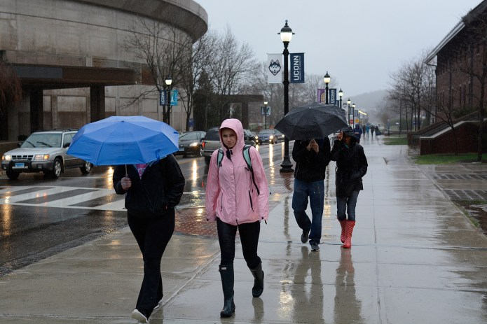 Students brave rainy conditions outside Gampel Pavilion. (Jason Jiang/The Daily Campus)