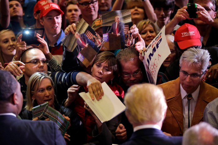 Supporters crowd around Republican presidential candidate Donald Trump as he signs autographs during a rally Tuesday, Feb. 23, 2016, in Reno, Nev. (AP)