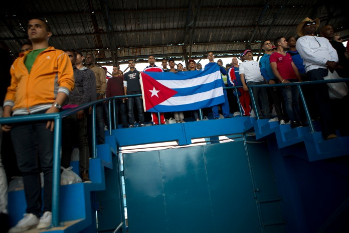 Cuban fans hold a flag as they await the start of a baseball game between the Tampa Bay Rays and the Cuban national baseball team, in Havana, Cuba, Tuesday, March 22, 2016. It's the first game featuring an MLB team in Cuba since the Baltimore Orioles played in the country in 1999. (AP Photo/Rebecca Blackwell)
