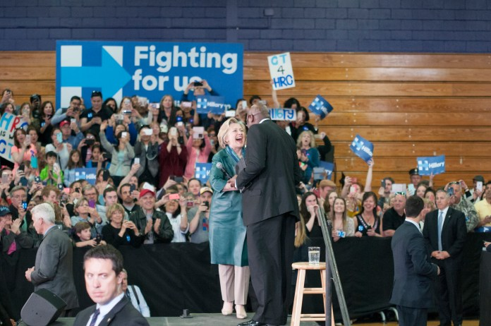 State Rep. Charlie Stallworth, D-Bridgeport, greets Democratic presidential candidate Hillary Clinton on the stage during a campaign rally at the University of Bridgeport on Sunday, April 24, 2016. (Kyle Constable/The Daily Campus)
