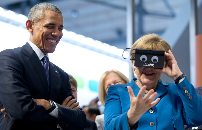 U.S. President Barack Obama looks on as German Chancellor Angela Merkel tests VR goggles when touring the Hannover Messe, the world's largest industrial technology trade fair, in Hannover, northern Germany, Monday, April 25, 2016. Obama is on a two-day official visit to Germany. (AP Photo/Carolyn Kaster)