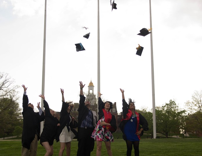 In this undated file photo, students toss their hats into the air for graduation on the Great Lawn in front of Wilbur Cross Building. (Amar Batra/Daily Campus)
