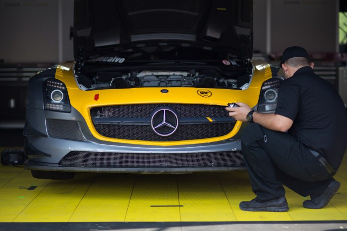 A team mechanic polishes a Mercedes SLS AMG GT3 in the paddock.(Jackson Haigis/Daily Campus)