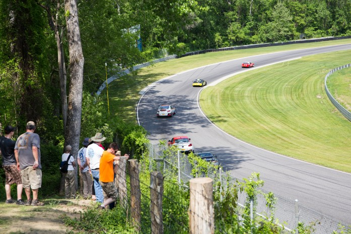 Spectators enjoy the shade and watch the Touring cars descend the downhill section of the track. There are over a dozen different places from which to watch the race, meaning that spectators can get many different perspectives of the track throughout the day.(Jackson Haigis/Daily Campus)