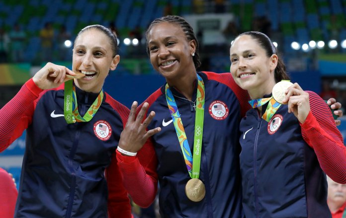 United States' Diana  Taurasi , left, Tamika Catchings, center, and Sue Bird, right, celebrate with their gold medals after their win in a women's basketball game against Spain at the 2016 Summer Olympics in Rio de Janeiro, Brazil, Saturday, Aug. 20, 2016. Taurasi and Bird are UConn alums. (Eric Gay/AP)