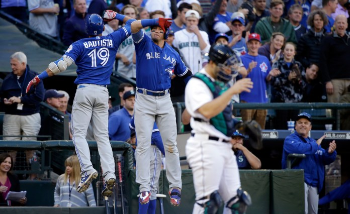 Toronto Blue Jays' Jose Bautista (19) is congratulated by Troy Tulowitzki as Seattle Mariners catcher Jesus Sucre looks away after Bautista's home run in the ninth inning of a baseball game Wednesday, Sept. 21, 2016, in Seattle. (Elaine Thompson/AP)