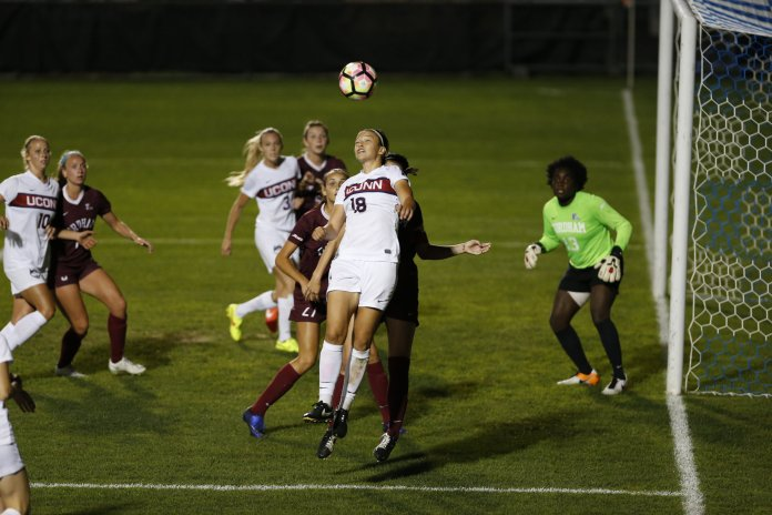 Redshirt senior Stephanie Ribeiro (18) heads a ball during a 4-1 win over Fordham on Thursday, Sept. 22 at Morrone Stadium. (Photo by Tyler Benton/The Daily Campus)