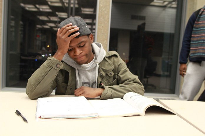 A stressed student studies at the Homer Babbidge Library on Dec. 5, 2013. (Mic Johnson/The Daily Campus)
