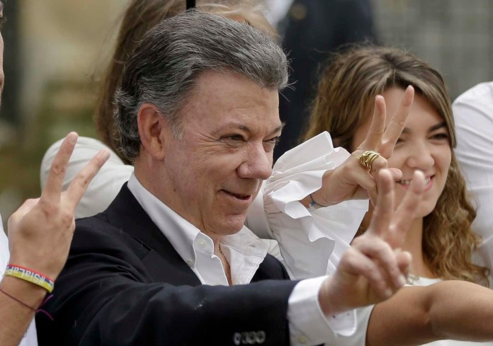 In this Sunday, Oct. 2, 2016 file photo Colombia's President Juan Manuel Santos makes the victory sign after voting in a referendum to decide whether or not to support the peace deal he signed with rebels of the Revolutionary Armed Forces of Colombia, FARC, in Bogota, Colombia. Santos was awarded the Noble Peace Prize for his effort. (Ricardo Mazalan/AP Photo)