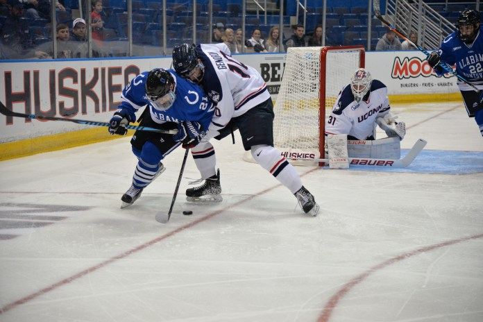 Sophomore defenseman Miles Gendron (10) fights Alabama-Huntsville forward Tyler Poulsen for a puck during the Huskies 4-0 shutout against the Colts on Saturday, Oct.8, 2016 during the team's season home opener at the XL Center in Hartford. The Huskies record moved to 2-0-2 following two road games this past week. (Amar Batra/The Daily Campus)