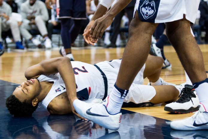 Sophomore guard Jalen Adams lays on the floor in pain in UConn's 70-67 overtime loss to Auburn on Friday, Dec. 23 at the XL Center in Hartford. Adams left the game seven minutes into the second half with a concussion and laceration, and while he returned to the bench later in the game as a spectator, it is unclear when he will return to playing basketball again. (Jackson Haigis/The Daily Campus)