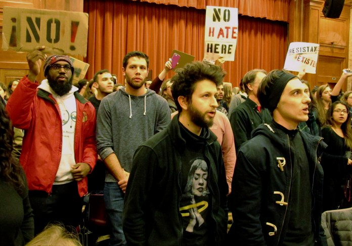 Middlebury College students turn their backs to Charles Murray, unseen, who they call a white nationalist, during his lecture in Middlebury, Vt., Thursday, March 2, 2017. Hundreds of college students on Thursday protested a lecture by a speaker they call a white nationalist, forcing the college to move his talk to an undisclosed campus location from which it was live-streamed to the original venue but couldn't be heard above protesters' chants, feet stamping and occasional smoke alarms. (Lisa Rathke/AP)