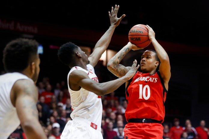 Cincinnati's Troy Caupain (10) shoots over Houston's Damyean Dotson, center, during the second half of an NCAA college basketball game, Thursday, March 2, 2017, in Cincinnati. Cincinnati won 65-47. (John Minchillo/AP)