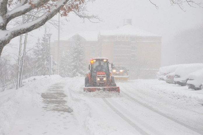 A tractor and snow plow are seen plowing near the Nathan Hale Inn and South campus during a snow storm on Friday, Feb. 5, 2016. UConn canceled all classes on all campuses for Friday, March 10. (Jason Jiang/The Daily Campus)
