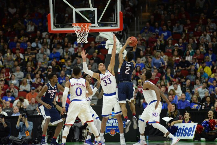 Jalen Adams attempts a shot over Kansas' Landen Lucas in the second round of the 2016 NCAA tournament in Des Moines, Iowa on March 19, 2016. The Jayhawks beat the Huskies 73-61. (Ashley Maher/The Daily Campus)
