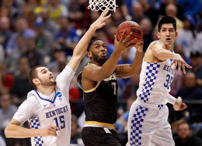 Wichita State's Rashard Kelly, center, heads to the basket as Kentucky's Isaac Humphries (15) and Derek Willis (35) defend during the first half of a second-round game in the men's NCAA college basketball tournament Sunday, March 19, 2017, in Indianapolis. (Jeff Roberson/AP)
