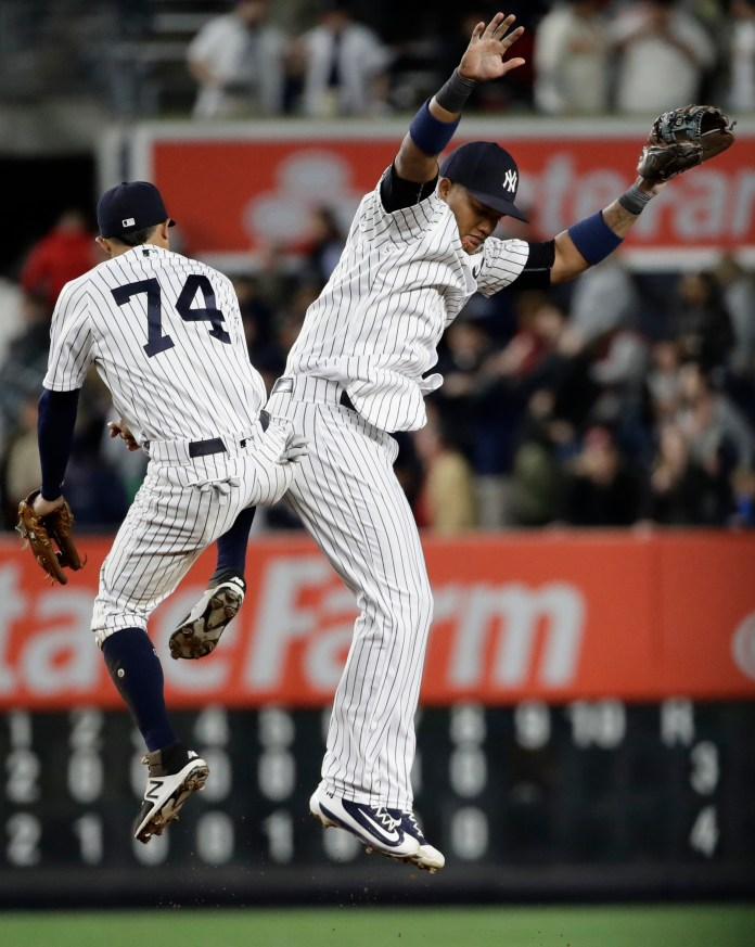 New York Yankees' Starlin Castro, right, celebrates with Ronald Torreyes (74) after a baseball game against the St. Louis Cardinals, Friday, April 14, 2017, in New York. (AP Photo/Frank Franklin II)