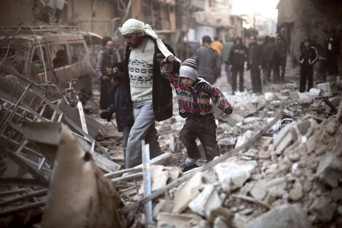This Dec. 24, 2015 file photo provided by Save the Children, a man walks with a pair of children in hand hand through the rubble in Eastern Ghouta,Syria.(Save the Children via AP, File)