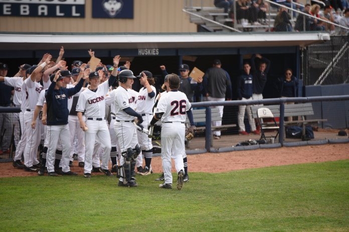 Junior Isaac Feldsteain (#26) is greeted by his teammates on the steps of the UConn dugout during Monday's game against Quinnipiac at J.O. Christian Field in Storrs, CT. (Zhelun Lang/The Daily Campus)