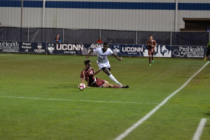Abdou Mbacke Thiam (#11) runs past a sliding defender in a win over Boston College 1-0 in overtime on Tuesday, October 18, 2016 at Morrone Stadium in Storrs, CT. (Amar Batra/The Daily Campus)