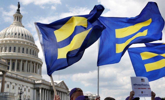 """In this July 26, 2017 file photo, people with the Human Rights Campaign hold up """"equality flags"""" during an event on Capitol Hill in Washington, in support of transgender members of the military. Officials say the Pentagon expects soon to ban transgender individuals from joining the military and to consider circumstances in which some currently serving transgendertroops could remain in uniform. (AP Photo/Jacquelyn Martin)"""