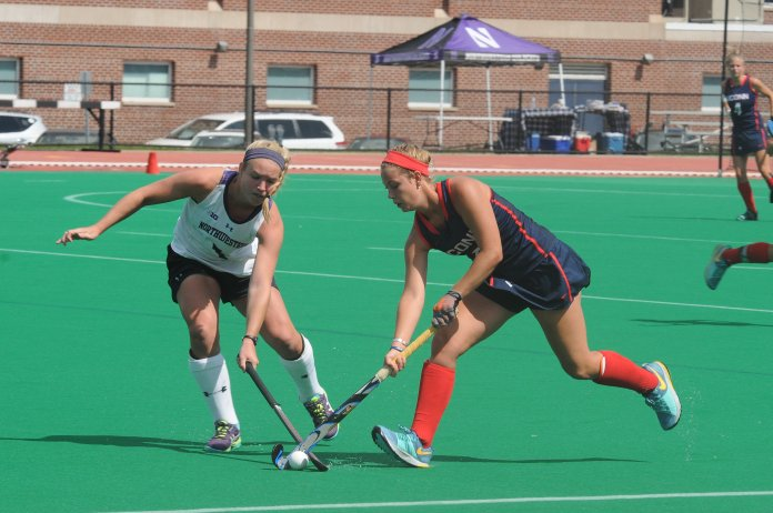 A UConn field hockey player battles for the ball during last year's win over Northwestern University. (Olivia Stenger/The Daily Campus)