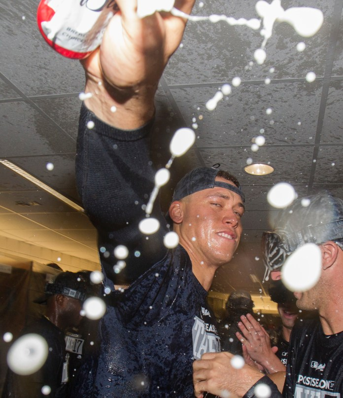 New York Yankees'Aaron Judge celebrates in the locker room after the team clinched a playoff berth by defeating the Toronto Blue Jays in a baseball game in Toronto, Saturday, Sept. 23, 2017. (Fred Thornhill/The Canadian Press via AP)